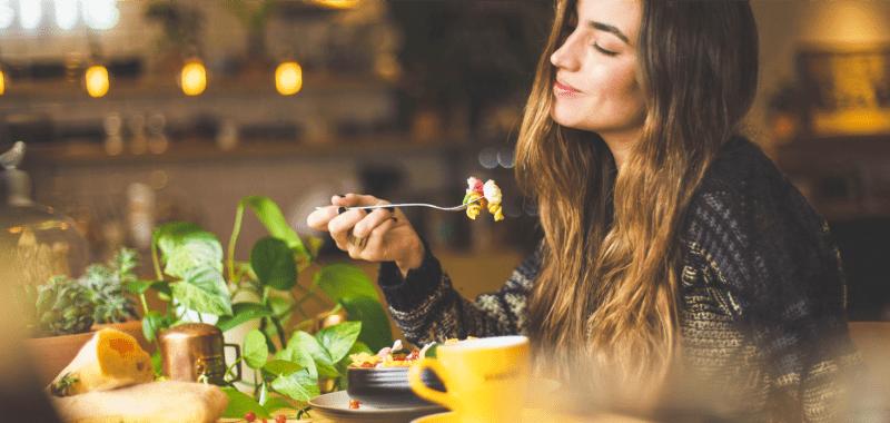 Une jeune femme mange au restaurant qu'elle a découvert grâce à Instagram
