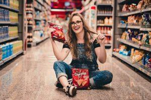 Jeune fille assise dans un rayon de supermarché avec des rackets de chips