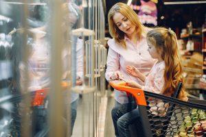 Mère et fille faisant les courses au super marché et en train de checker leur liste de course